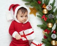 在圣诞节装饰的婴孩画象,穿戴作为圣诞老人,谎言在毛皮在杉树和戏剧与礼物,寒假概念附近 库存照片