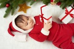 在圣诞节装饰的婴孩画象,穿戴作为圣诞老人,谎言在毛皮在杉树和戏剧与礼物,寒假概念附近 库存图片