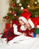 在圣诞节装饰,寒假概念的两个女孩画象,装饰了杉树和礼物 免版税图库摄影