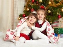 在圣诞节装饰,寒假概念的两个女孩画象,装饰了杉树和礼物 库存照片