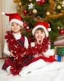 在圣诞节装饰,寒假概念的两个女孩画象,装饰了杉树和礼物 免版税库存图片