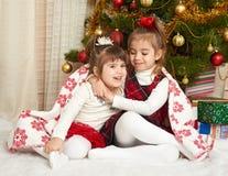在圣诞节装饰,寒假概念的两个女孩画象,装饰了杉树和礼物 免版税库存照片
