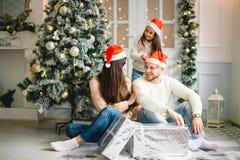 在圣诞节设置的年轻美丽的家庭 母亲、父亲和女儿 库存图片