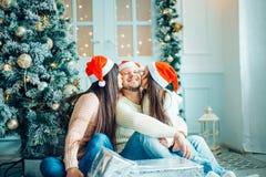 在圣诞节设置的年轻美丽的家庭 母亲、父亲和女儿 免版税库存照片