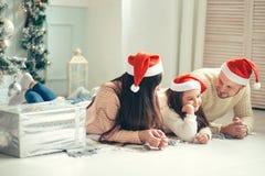 在圣诞节说谎在床上的圣诞老人帽子的家庭 获得母亲的父亲和的婴孩乐趣 库存照片