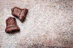 在圣诞节铃声形状的巧克力糖用搽粉的糖 库存照片