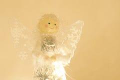 在圣诞节闪耀的结构树上面的天使 免版税库存照片