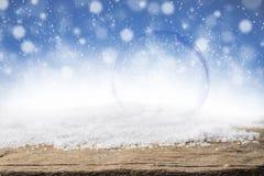在圣诞节雪和木头背景的空的玻璃泡影 免版税库存图片