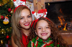 在圣诞节,佩带鹿帽子和妈妈的litle女孩的愉快的母亲和微笑daugher圣诞节帽子,有室内的 免版税库存照片
