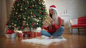 在圣诞节,美女发现了一件礼物在树下 概念:魔术,圣诞节,礼物,假日 股票视频