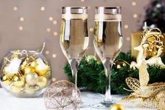 在圣诞节bokeh背景的两块香槟玻璃 免版税库存图片