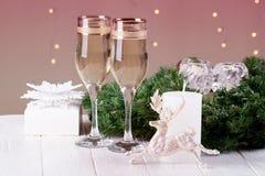 在圣诞节bokeh背景的两块香槟玻璃 免版税库存照片