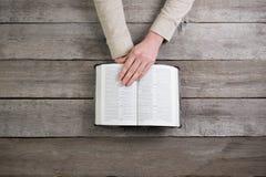 在圣经的妇女手 她是读和祈祷在圣经 免版税库存照片