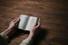 在圣经的妇女手 她读并且祈祷 免版税库存照片