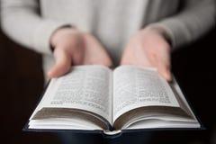 在圣经的妇女手 她读并且祈祷 库存照片