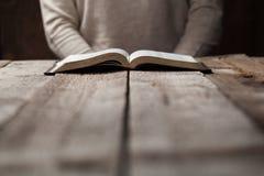 在圣经的妇女手 她读并且祈祷 免版税库存图片