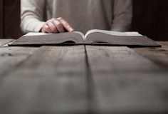 在圣经的妇女手 她读并且祈祷 免版税图库摄影