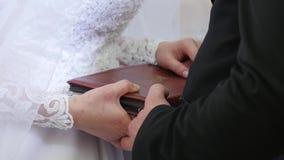 在圣经的新娘和新郎手 新娘和新郎在圣经安置他们的手对交换誓愿 免版税库存照片
