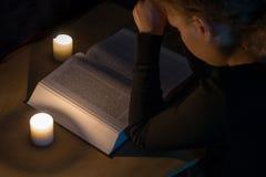 在圣经的祈祷的女孩与由烛光的一个十字架 免版税库存照片