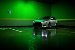 在地下停车场的灰色汽车逗留和在湿沥青反射 库存照片