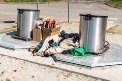 在地下大型垃圾桶罐头倾销的堆老衣裳和鞋子作为,乱丢和污染都市城市的破烂物和垃圾 免版税图库摄影