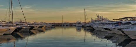 在地中海口岸的小船在日落、反射在水和美丽的天空,门门户,马略卡,西班牙 免版税库存照片