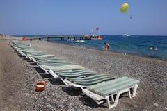 在地中海手段pebbled海滩的Sunbeds  免版税库存照片