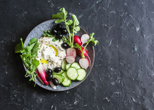 在地中海样式的健康饮食快餐-希腊酸奶,萝卜,橄榄,黄瓜,在黑暗的背景,顶视图的莴苣 免版税图库摄影