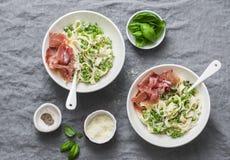 在地中海样式的午餐桌 意大利细面条面团用乳脂状的调味汁、绿豆和熏火腿在灰色背景 库存照片