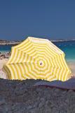 在地中海海滩的黄色遮阳伞伞用绿松石水,在海边概念的暑假 免版税图库摄影