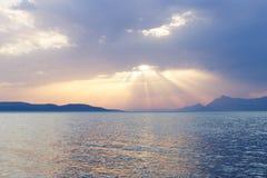 在地中海的夏天日落有岩质岛的在背景中 免版税库存照片