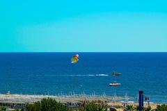 在地中海的海滩 游人飞行在降伞的海在小船后 图库摄影