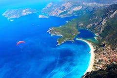 在地中海的蓝色盐水湖的滑翔伞飞行 降伞的红色圆顶反对蓝色海的 火鸡 Oludeniz 免版税库存图片