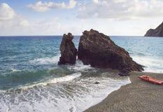 在地中海的重的岩石,由与一艘红色救生艇的一个海滩 免版税库存图片