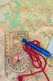 在地图和抢救口哨的指南针 免版税图库摄影