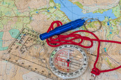 在地图和抢救口哨的指南针 库存照片