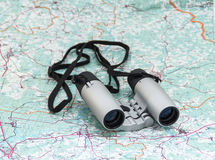 在地图的双筒望远镜 免版税库存图片