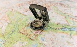 在地图的指南针发现的方式在原野和生活中 库存图片