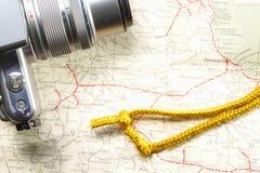 在地图的照相机和金绳索 免版税库存照片