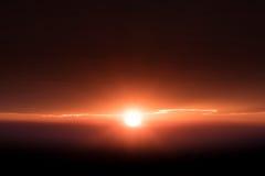 在地平线亮光光芒外缘光的太阳在边缘云彩 免版税库存照片