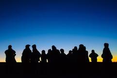 在地平线和剪影人民的第一阳光 免版税图库摄影
