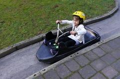在地平线罗托路亚无舵雪橇的女孩乘驾 免版税库存照片