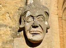 在地方教会的古老石面貌古怪的人 图库摄影