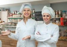 在地方糖果店的女职工提供的甜点 免版税库存照片