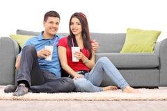 年轻在地板上供以座位的夫妇饮用的鸡尾酒 库存照片