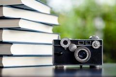 在地板上和照相机把放的书 白革书和研究 免版税图库摄影