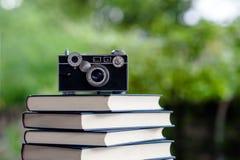 在地板上和照相机把放的书 白革书和研究 库存图片