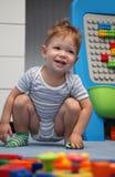 在地板上的一个愉快的男婴 免版税库存照片