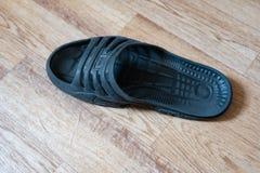 在地板上的一个黑男性拖鞋 免版税图库摄影