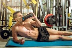在地板上的人饮用的蛋白质震动 免版税库存图片